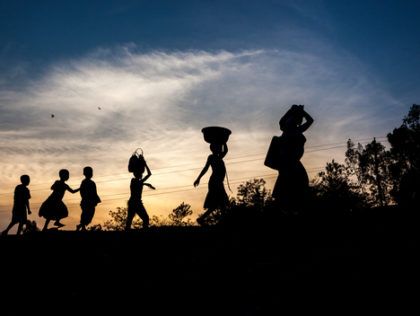Women and children walk at sunset on a road near Uvira, Democratic Republic of the Congo (DRC), one of the main transit points for Burundian refugees crossing the border.